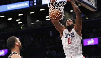 Los Angeles Clippers center DeAndre Jordan (6) dunks in front of two Nets defenders during the first half of an NBA basketball game, Monday, Feb. 12, 2018, in New York. (AP Photo/Kathy Willens)