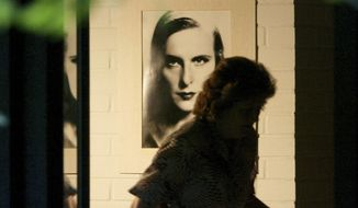 FILE - In this file photo dated Tuesday, Sept. 9, 2003, an unidentified housekeeper, passes by a picture of famous film director Leni Riefenstahl on the wall in Riefenstahl's home in Poecking, Germany, after she died Monday at the age of 101.  A German cultural foundation said Monday Feb. 12, 2018, that it has been bequeathed photos, films, manuscripts, letters and files from the estate of Leni Riefenstahl, the legendary filmmaker best known for the propaganda movies she made for Nazi Germany. (AP Photo/Jan Pitman, FILE)