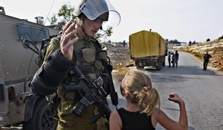 FILE - In this Nov. 2, 2012 file photo, then 12-year-old Ahed Tamimi tries to punch an Israeli soldier during a protest in the West Bank village of Nabi Saleh. Tamimi is to go on trial Tuesday, Feb. 13, 2018, before an Israeli military court, for slapping and punching two Israeli soldiers in December. Palestinians say her actions embody their David vs. Goliath struggle against a brutal military occupation, while Israel portrays them as a staged provocation meant to embarrass its military. Tamimi is one of an estimated 350 Palestinian minors in Israeli jails. (AP Photo/Majdi Mohammed, File)