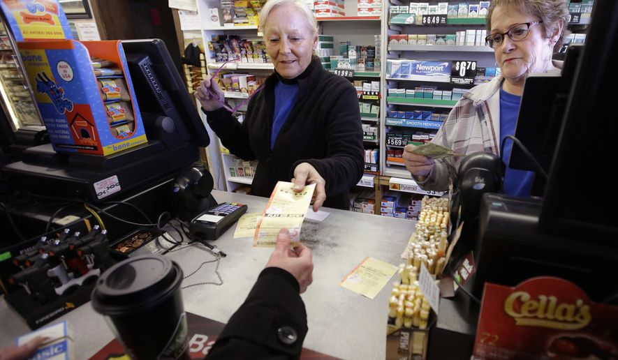 FILE - In this Jan. 7, 2018, file photo, cashiers Kathy Robinson, left, and Ethel Kroska, right, both of Merrimack, N.H., sell a lottery ticket at Reeds Ferry Market convenience store in Merrimack. A woman who bought the winning ticket there, and identified as in court documents as Jane Doe, won the $559.7 million jackpot and has filed a complaint in Nashua asking that a judge allow her to stay anonymous. The commission wants the complaint dismissed. The case will be heard Tuesday, Feb. 13. (AP Photo/Steven Senne, FIle)