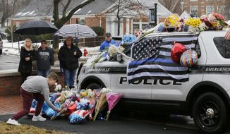 Mourners gather and leave flowers on a police cruiser parked in front of City Hall in Westerville, Ohio, on Sunday, Feb. 11, 2018. Westerville police officers Anthony Morelli and Eric Joering were killed in the line of duty Saturday when a suspect opened fire on them as they responded to a call at a residence. (Sam Greene/The Cincinnati Enquirer via AP)