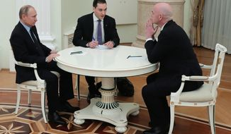 Russian President Vladimir Putin, left, speaks to FIFA president Gianni Infantino, right, during their meeting in the Kremlin in Moscow, Russia, Monday, Feb. 12, 2018. (Mikhail Klimentyev/Pool Photo via AP)