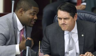 FILE - In this March 9, 2017, file photo, Rep. Byron Donalds, R-Naples, left, confers with Rep. Cord Byrd, R-Neptune Beach, in Tallahassee, Fla. Donalds is the lead sponsor of a proposal that would allow parents whose children have been bullied at public schools to obtain state vouchers to help pay tuition at a private school. (AP Photo/Steve Cannon, File)