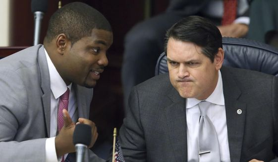 In this March 9, 2017, file photo, Rep. Byron Donalds, R-Naples, left, confers with Rep. Cord Byrd, R-Neptune Beach, in Tallahassee, Fla. Donalds is the lead sponsor of a proposal that would allow parents whose children have been bullied at public schools to obtain state vouchers to help pay tuition at a private school. (AP Photo/Steve Cannon, File)