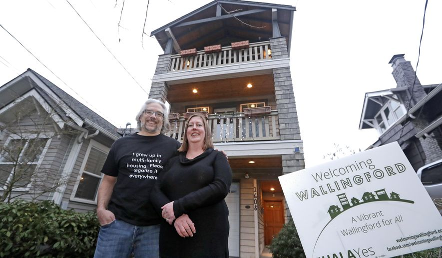 In this Thursday, Jan. 11, 2018, photo, Bryan Kirschner, left, and his wife, Holly Ferguson, supporters of a proposed development plan, stand in front of their tall, narrow house, which sits adjacent to older, traditional homes, in Seattle. A massive influx of new residents and an ensuing housing crunch has led to skyrocketing rents and home prices that have strained middle- and working-class families and deepened the city's crisis of homelessness. (AP Photo/Elaine Thompson)