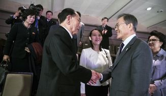 In this photo provided by South Korea Presidential Blue House, South Korean President Moon Jae-in, right, shakes hands with North Korea's nominal head of state Kim Yong Nam as Kim Yo Jong, center, North Korean leader Kim Jong Un's sister, watches after a performance of North Korea's Samjiyon Orchestra at National Theater in Seoul, South Korea, Sunday, Feb. 11, 2018. (Presidential Blue House via AP)