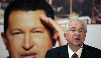 FILE - In this Jan. 29, 2013 file photo, Venezuela's Oil Minister Rafael Ramirez attends a signing ceremony with the Russian energy company Rosneft in Caracas, Venezuela, in front of a large image of Venezuela's President Hugo Chavez. U.S. prosecutors believe Ramirez received bribes as part of an alleged multibillion-dollar graft scheme in Venezuela's oil industry, an official familiar with the U.S. investigation said Monday, Feb. 12, 2018. Ramirez has called a separate criminal Venezuelan probe retaliation for his decision to break with Venezuela's President Nicolas Maduro, who he has accused of running Venezuela's once-thriving oil industry into the ground and abandoning the socialist ideals of the late Hugo Chavez. (AP Photo/Ariana Cubillos, File)
