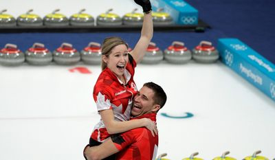 Canadians Kaitlyn Lawes and John Morris celebrate after winning the gold medal against Switzerland in the debut of mixed doubles curling on Tuesday.
