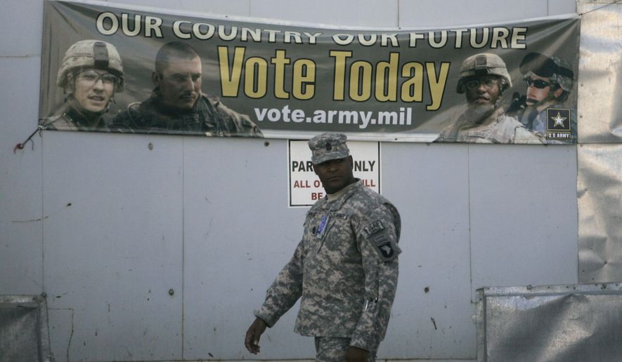 A U.S member of Combined Joint Task Force-101 walks past an election banner at a US military base in Bagram north of Kabul, Afghanistan, Wednesday, Oct. 15, 2008.  Soldiers, aid workers and military contractors in Afghanistan are filling out absentee ballots this week and sending them back to the states in hopes they arrive in time to be counted by elections officials. (AP Photo/Rafiq Maqbool)