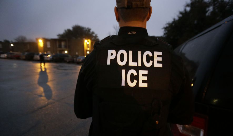 U.S. Immigration and Customs Enforcement agents enter an apartment complex looking for a specific undocumented immigrant convicted of a felony during an early morning operation in Dallas. (AP Photo/LM Otero, File) ** FILE **