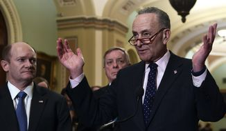 Senate Minority Leader Sen. Chuck Schumer of N.Y., right, responds to a reporter's question on Capitol Hill in Washington, Tuesday, Feb. 13, 2018, following the weekly Democratic policy luncheon. Schumer is joined by, Sen. Chris Coons, D-Del., left, and Sen. Dick Durbin, D-Ill., center.(AP Photo/Susan Walsh)