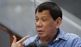 "Philippine President Rodrigo Duterte gestures while addressing Filipino Overseas Workers who were repatriated from Kuwait, Tuesday, Feb. 13, 2018 at the Ninoy Aquino International Airport in suburban Pasay city southeast of Manila, Philippines. Human rights groups condemned the Philippine president Tuesday for his remarks about troops shooting female communist rebels in the genitals to render them ""useless,"" which they said can encourage sexual violence and war crimes. (AP Photo/Bullit Marquez)"