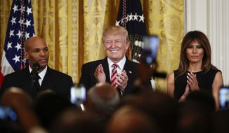 President Donald Trump, center, and first lady Melania Trump, right, applaud as Surgeon General Jerome Adams, left, speaks during the National African American History Month reception in the East Room of the White House in Washington, Tuesday, Feb. 13, 2018. (AP Photo/Carolyn Kaster)