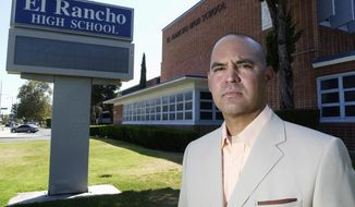 FILE - In this July 21, 2010, file photo, teacher Gregory Salcido poses in front of El Rancho High School in Pico Rivera, Calif. A Los Angeles-area city council will consider a resolution Tuesday, Feb. 13, 2018, asking for the resignation of councilman Salcido, who bashed U.S. military service members while teaching to a high school class. (Keith Durflinger/Los Angeles Daily News via AP)