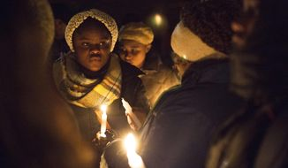 Dozens of people braved the freezing temperature to gather together and hold a vigil for Mujey Dumbuya, 16, at her bus stop across the street from the Chicken Coop on Eastern Ave SE in Grand Rapids, Michigan, on Thursday, Feb. 1, 2018. Dumbuya, a student at East Kentwood High School, was murdered last week. The identity of the murderer or murderers is still currently unknown. (Casey Sykes /The Grand Rapids Press via AP)