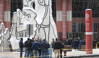Police guard the crime scene after an off-duty Chicago police officer was shot at the James R. Thompson Center,  in Chicago, Tuesday, Feb. 13, 2018. Spokesman Anthony Guglielmi says the off-duty officer was shot around 2 p.m. Tuesday at the James R. Thompson Center. Guglielmi says the preliminary information is that the shooting happened just outside the building. The officer was transported to Northwestern Memorial Hospital. (John J. Kim/Chicago Tribune via AP)