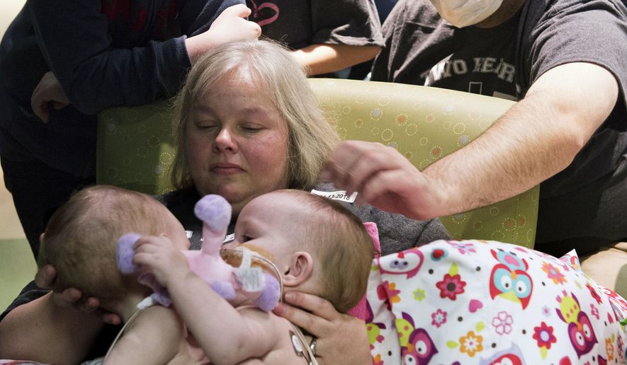 In this Jan. 13, 2018, photo provided by Texas Children's Hospital in Houston, Jill and Michael Richards along with their two sons, Collin and Seth, spend time together with their conjoined twins, Anna and Hope Richards, before successful surgery to separate the toddler girls. The two were born in 2016 conjoined at the chest and abdomen. (Paul Vincent Kuntz/Texas Children's Hospital via AP)