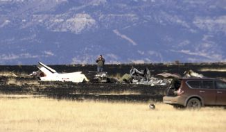 FILE--This Jan. 19, 2018, file image taken from video shows an investigator photographing the scene near Raton, N.M., where a helicopter crashed. The lone survivor of a New Mexico helicopter crash last month that killed five people, including key Zimbabwean opposition leader Roy Bennett, recalls that the aircraft hit the ground with a loud bang before rolling forward and coming to a stop upside down.(AP Photo/Peter Banda, file)