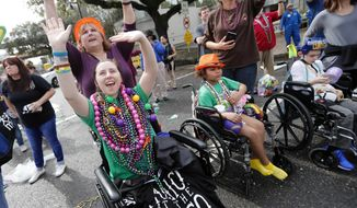 Patients from Children's Hospital of New Orleans wave for beads and trinkets outside the facility during the Krewe of Thoth Mardi Gras parade in New Orleans, Sunday, Feb. 11, 2018. The krewe's original parade route was designed specifically to serve people who were unable to attend other parades in the city. The route is designed to pass in front of several extended healthcare facilities.Carnival season will culminate on Mardi Gras day this Tuesday, Feb. 13. (AP Photo/Gerald Herbert)