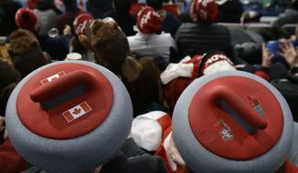 Spectators sport headwear shaped as curling stones as they watch the mixed doubles curling finals match against Canada and Switzerland at the 2018 Winter Olympics in Gangneung, South Korea, Tuesday, Feb. 13, 2018. (AP Photo/Aaron Favila)