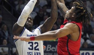 Richmond's Khwan Fore, right, attempts to block a shot by Rhode Island's Jared Terrell (32) during the first half of an NCAA college basketball game Tuesday, Feb. 13, 2018, in Kingston, R.I. (AP Photo/Stew Milne)