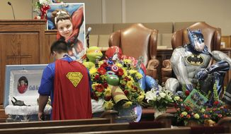 FILE - This Oct. 5, 2016 file photo shows Dale Hall, dressed as Superman, next to the casket for his brother, Jacob Hall at Oakdale Baptist Church on Wednesday, Oct. 5, 2016, in Townville, S.C. A teenager charged with killing his father at their home and a first-grader on a school playground said he kissed his bunny Floppy and three dogs goodbye after shooting his father and then headed to the school to resume shooting, according to the boy's videotaped statement played in court Monday, Feb. 12, 2018. (Ken Ruinard/The Independent-Mail via AP, Pool)