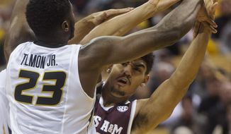 Texas A&M's Tyler Davis, right, tries to pass around Missouri's Jeremiah Tilmon, left, during the first half of an NCAA college basketball game Tuesday, Feb. 13, 2018, in Columbia, Mo. (AP Photo/L.G. Patterson)