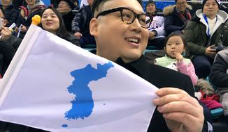 A Kim Jong Un impersonator, calling himself only Howard from Australia, holds a unification flag while attending the Korea-Japan womens ice hockey game at the 2018 Winter Olympics in Pyeongchang, South Korea, Wednesday, Feb. 14, 2018.  (AP Photo/Eric Talmadge)