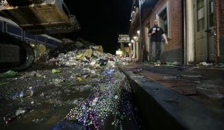 FILE - In this Feb. 13, 2013 file photo, people walk past debris debris on Bourbon Street in the early morning of Ash Wednesday, the day after Mardi Gras, in the French Quarter of New Orleans. Mardi Gras produces fun-filled days of merriment, joy and the occasional hangover. It also produces a lot of garbage. But this year two New Orleans organizations aimed to change that with a pilot recycling project to collect cans, plastic bottles and that Mardi Gras accessory found hanging on fences, trees, and balconies: beads. (AP Photo/Gerald Herbert)