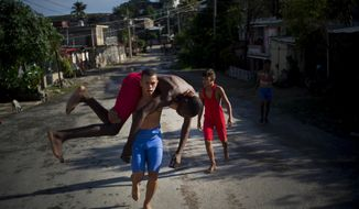 "In this Jan. 22, 2018 photo, young wrestlers train in the street during the week-long student wrestling championship coined ""The truth of my neighborhood,"" organized by locals in the Chicharrones neighborhood of Santiago, Cuba. In this neighborhood, a wrestling-loving local man created a homegrown, neighborhood-backed program to support aspiring wrestlers from Cuba's economically struggling provinces. (AP Photo/Ramon Espinosa)"