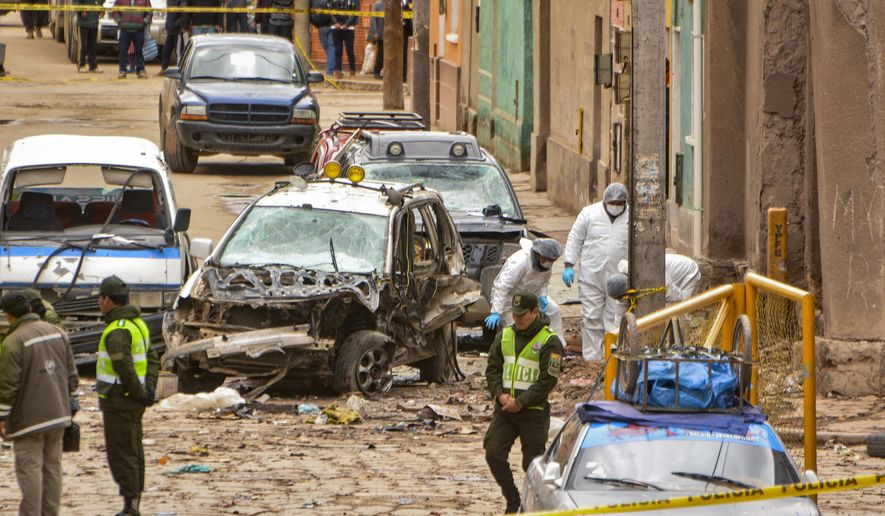 Police inspect the site of an explosion that killed four people, in Oruro, Bolivia, Wednesday, Feb. 14, 2018. Bolivia's Defense Minister Javier Zabaleta says an explosive was used in a blast that went off Tuesday night, the second deadly explosion to hit the city of Oruro during Carnival celebrations. (AP Photo/Emilio Huascar)