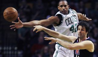 Los Angeles Clippers guard Milos Teodosic, right, passes the ball as he is pressured by Boston Celtics forward Al Horford (42) during the second quarter of an NBA basketball game in Boston, Wednesday, Feb. 14, 2018. (AP Photo/Charles Krupa)