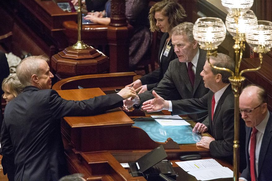 Gov. Bruce Rauner reaches out to shake hands with House Speaker Michael Madigan, D-Chicago, right middle, and Senate President John Cullerton, D-Chicago, after delivering his budget address to a joint session of the General Assembly Wednesday, Feb. 14, 2018 at at the Capitol in Springfield, Ill.  (Rich Saal/The State Journal-Register via AP)