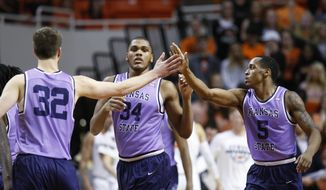 Kansas State forward Dean Wade (32), forward Levi Stockard III (34) and guard Barry Brown (5) celebrate as they walk off the court during a timeout in the second half of an NCAA college basketball game against Oklahoma State in Stillwater, Okla., Wednesday, Feb. 14, 2018. (AP Photo/Sue Ogrocki)