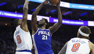 Philadelphia 76ers' Joel Embiid (21) pulls in a rebound over New York Knicks' Kyle O'Quinn (9) and Michael Beasley (8) in the second half of an NBA basketball game, Monday, Feb 12, 2018, in Philadelphia. The 76ers won 108-92. (AP Photo/Michael Perez)