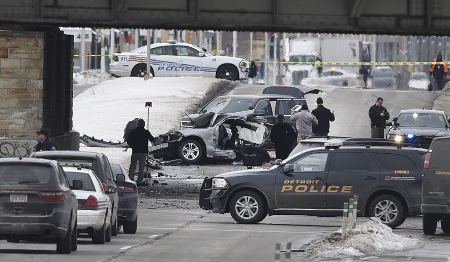 Detroit police investigators work at the scene of a crash at Clark Street and Michigan Avenue in Detroit Tuesday, Feb. 13, 2018. Detroit police officer Darren Weathers, 25, died in the crash. He was alone in the car and was involved in a training exercise, Chief James Craig said. The cause of the crash is still under investigation. (Max Ortiz/Detroit News via AP)
