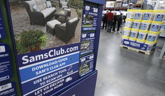 FILE- In this June 4, 2015, file photo, a sign encouraging shoppers to use a Sam's Club phone app is displayed at one of the company's stores in Bentonville, Ark. Starting Wednesday, Feb. 14, 2018, the Walmart-owned warehouse club will give free shipping on online orders for Plus members on 95 percent of the items it sells. (AP Photo/Danny Johnston, File)