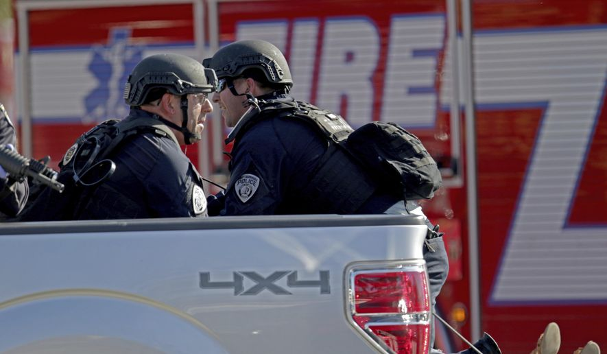 Police officers ride in the back of a pickup truck as they tend to a victim following a shooting at Marjory Stoneman Douglas High School in Parkland, Fla., on Wednesday, Feb. 14, 2018. (John McCall/South Florida Sun-Sentinel via AP)