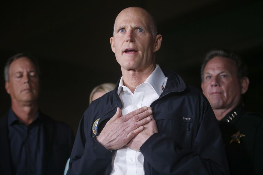 Florida Gov. Rick Scott gestures as he speaks during a news conference near Marjory Stoneman Douglas High School in Parkland, Fla., where a former student is suspected of killing at least 17 people Wednesday, Feb. 14, 2018. The shooting at a South Florida high school sent students rushing into the streets as SWAT team members swarmed in and locked down the building. Police were warning that the shooter was still at large even as ambulances converged on the scene and emergency workers appeared to be treating those possibly wounded. (AP Photo/Wilfredo Lee)