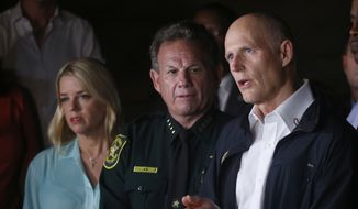 Florida Gov. Rick Scott, foreground, speaks along with Sheriff Scott Israel, center, of Broward County, and Pam Bondi, Florida Attorney General, during a news conference near Marjory Stoneman Douglas High School in Parkland, Fla., where a former student is suspected of killing at least 17 people Wednesday, Feb. 14, 2018. (AP Photo/Wilfredo Lee)