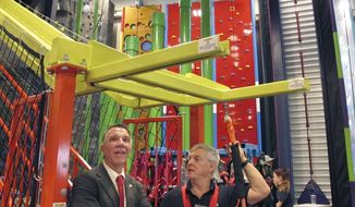 Vermont Gov. Phil Scott, left, visits a new climbing gym and movie theater, Wednesday, Feb. 14, 2018, at Jay Peak resort in Jay, Vt., two years after the ski area was rocked by an investment fraud. (AP Photo/Lisa Rathke)