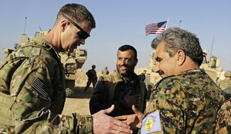FILE - This Wednesday, Feb. 7, 2018 file photo, shows U.S. Army Maj. Gen. Jamie Jarrard left, thanks Manbij Military Council commander Muhammed Abu Adeel near the town of Manbij, northern Syria. As Syrian troops and their allies push toward final victory and the battle against Islamic State militants draws to an end, new fronts are opening up, threatening an even broader confrontation. The U.S., Israel and Turkey all have deepened their involvement, seeking to protect their interests in the new Syria order. (AP Photo/Susannah George, File)