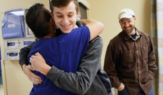 In this Jan. 31, 2018 photo, Jarom Oilar hugs Dr. Thomas Etter at West Park Hospital, as his father Josh Oilar looks on in Cody, Wyo. Etter was one of the emergency surgeons who stabilized Jarom after he was severely injured by an explosion two years ago. (Amber Peabody/The Cody Enterprise via AP)