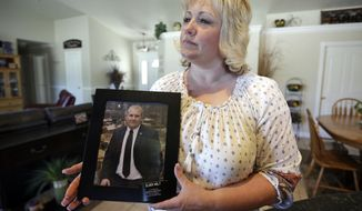 FILE - In this July 13, 2016 file photo, Laurie Holt holds a photograph of her son Josh Holt at her home, in Riverton, Utah. A 7-year-old Venezuelan girl has finally made it to the United States after a long fight to take her away from the turbulent South American nation where her jailed mother and American boyfriend work to recover their freedom. The jailed couple decided the girl, Nathalia Carrasco, would be better off in Utah with Holt's parents than in the shortage-stricken Venezuela. She was living with her grandmother. (AP Photo/Rick Bowmer, File)