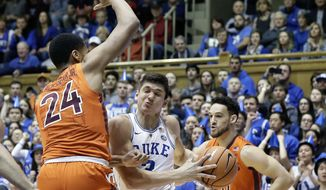 Duke's Grayson Allen drives to the basket while Virginia Tech's Kerry Blackshear Jr. (24) and Devin Wilson defend during the first half of an NCAA college basketball game in Durham, N.C., Wednesday, Feb. 14, 2018. (AP Photo/Gerry Broome)