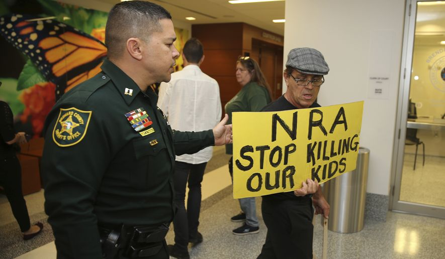 A Broward County sheriff's deputy escorts a protestor away from the door of the courtroom where a hearing was held for school shooting suspect Nikolas Cruz, Thursday, Feb. 15, 2018, at Broward County Court in Fort Lauderdale, Fla.  Cruz is accused of opening fire Wednesday at Marjory Stoneman Douglas High School in Parkland, Fla., killing more than a dozen people and injuring several.   (Charles Trainor Jr./Miami Herald via AP, Pool)