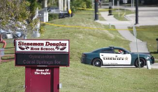 Law enforcement officers blocked off the entrance to Marjory Stoneman Douglas High School in Parkland, Florida, on Thursday. Nikolas Cruz was charged with 17 counts of premeditated murder. (Associated Press)