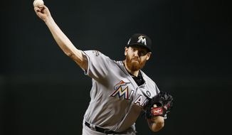 FILE - In this Sunday, Sept. 24, 2017 file photo, Miami Marlins' Dan Straily warms up during the first inning of a baseball game against the Arizona Diamondbacks in Phoenix. Pitcher Dan Straily and Miami argued their arbitration case Thursday, Feb. 15, 2018. Straily, eligible for the first time, asked for a raise from $552,100 to $3.55 million from James Darby, Sylvia Skratek and Francis. The Marlins argued for $3,375,000. (AP Photo/Ross D. Franklin, File)