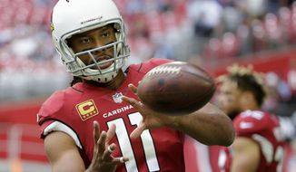 """FILE - In this Dec. 10, 2017, file photo, Arizona Cardinals wide receiver Larry Fitzgerald warms up prior to an NFL football game against the Tennessee Titans in Glendale, Ariz. New Arizona coach Steve Wilks says Fitzgerald has told him he'll return for a 15th NFL season. Wilks made the comment Thursday, Feb. 15, 2018, in an interview on the """"Doug &Wolf"""" sports talk radio show. (AP Photo/Rick Scuteri, File)"""