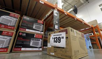 FILE - In this Aug. 1, 2017 file photo, fans and air conditioners are seen for sale at a hardware store in Seattle. A federal judge in San Francisco on Thursday, Feb. 15, 2018, has ordered the Trump administration to implement energy-use limits for portable air conditioners and other products that were adopted during the last days of the Obama presidency. (AP Photo/Elaine Thompson, File)